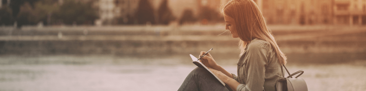 Person writing outdoors in a notebook