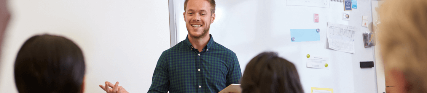 A male teacher in front of a whiteboard