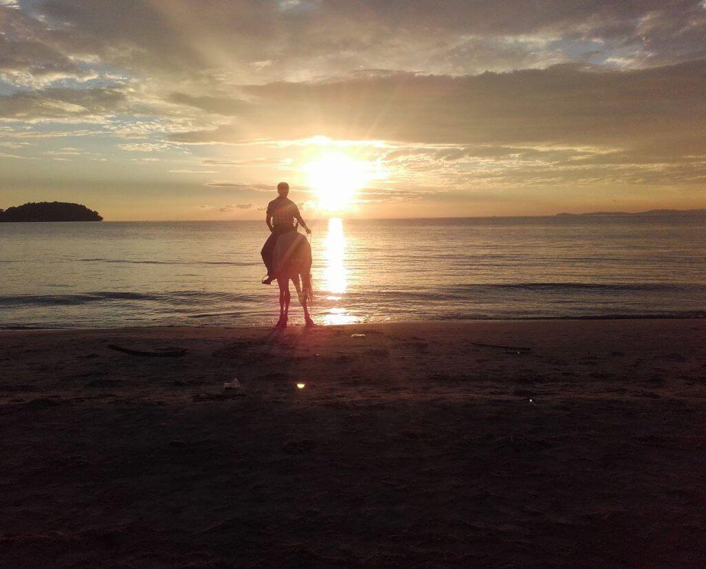 Daniel's friend on a horse at a beach in Cambodia