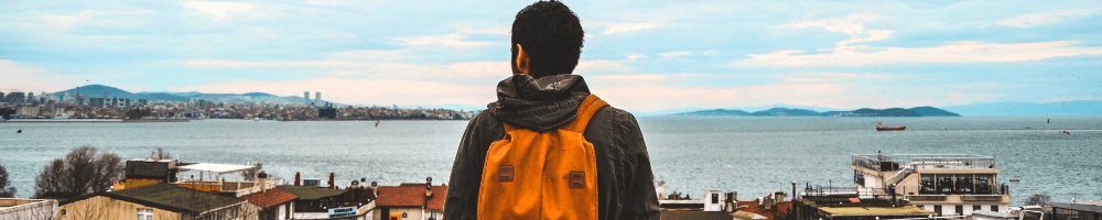 Man with backpack looking out onto a bay