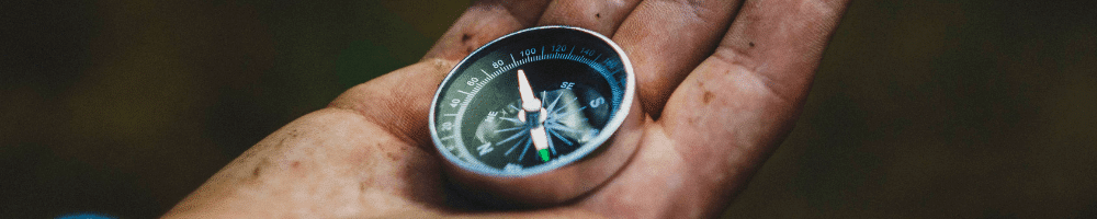Dirty hand holding a compass