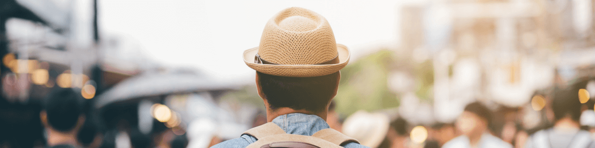 The back of a man wearing a hat and backpack in a crowd of people