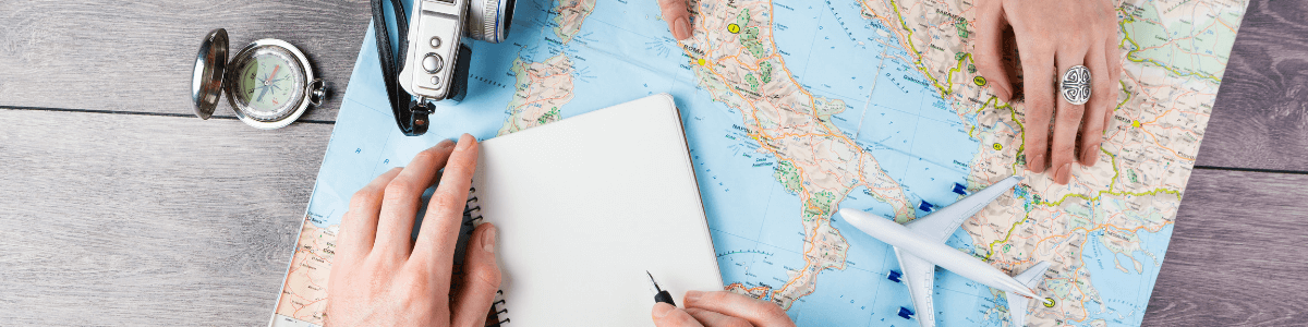 A person writing in a notebook lying on top of a map