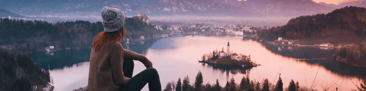A woman looking over a lake at dusk