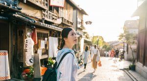 traveler stopped on the street and looking at the Japanese traditional building. Japan travel tourist woman on vacation in Kyoto shopping in alley.