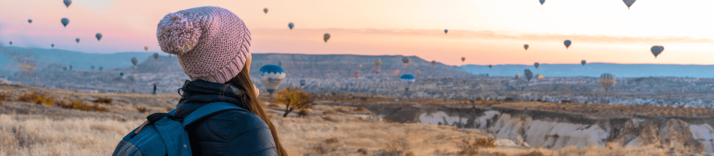 A woman looking at hot air balloons in the sky