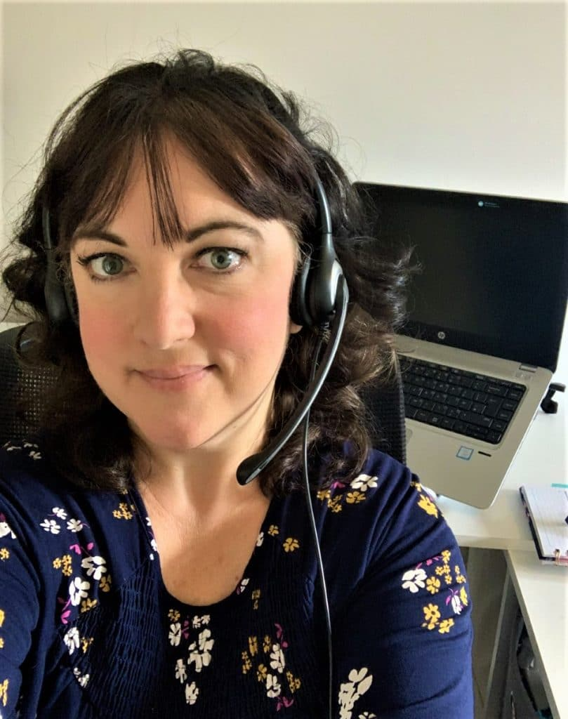 Online English teacher, Claire, wearing a headset and sitting in front of her laptop
